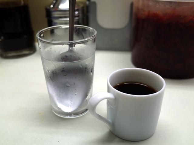 お冷やのグラスに刺されたスプーンとコーヒー