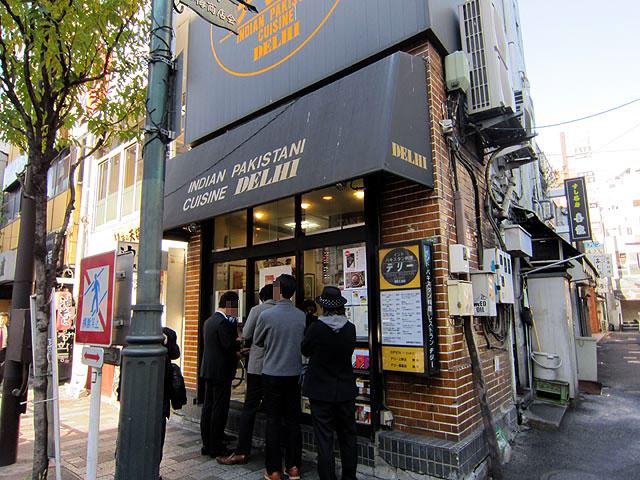 黒い看板のデリー上野店の外観。行列店です