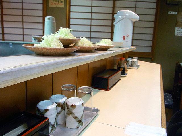 店内カウンター上に積まれたキャベツが盛られた皿