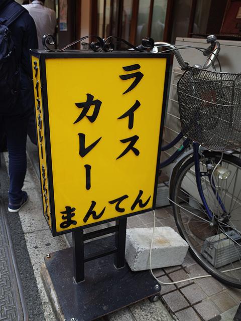 「ライスカレーまんてん」と書かれた店頭の黄色い立看板